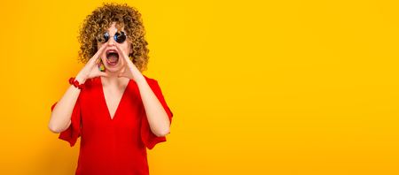 Portrait of a white woman with afrro curly hairstyle in red dress and sunglasses screaming through her palms isolated on orange background with copyspace making announcement concept horizontal picture. Stock Photo