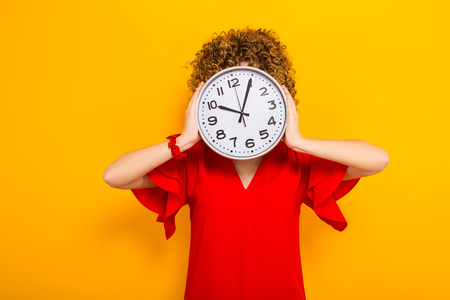 Portrait of a white woman with afrro curly hairstyle in red dress and sunglasses covering her head with watches isolated on orange background with copyspace punctuality being on time or late concept. Stock Photo