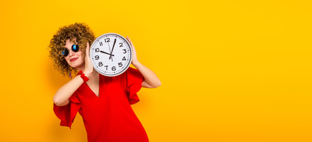 Portrait of a white woman with afrro curly hairstyle in red dress and sunglasses hiding behind watches isolated on orange background with copyspace punctuality being on time or late concept horizontal. Stock Photo