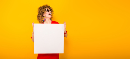 Portrait of a white woman with afrro curly hairstyle in red dress and sunglasses holding white blank board isolated on orange background your text here concept horizontal picture.