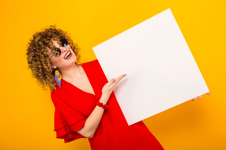 Portrait of a white woman with afrro curly hairstyle in red dress and sunglasses pointing at white blank board isolated on orange background your text here concept.