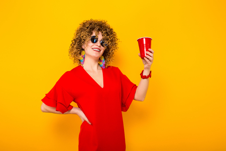 Portrait of a white woman with afrro curly hairstyle in red dress and sunglasses holding red plastic cup with drink isolated on orange background with copyspace celebration concept. Stock Photo