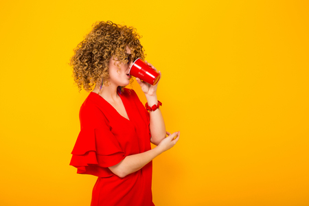 Portrait of a white woman with afrro curly hairstyle in red dress and sunglasses drinking from red plastic cup with drink isolated on orange background with copyspace celebration concept. Stock Photo