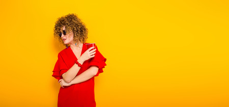 Portrait of a white woman with afrro curly hairstyle in red dress and sunglasses holding red plastic cup with drink and looking aside isolated on orange background with copyspace celebration concept. Stock Photo