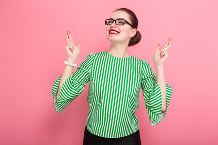 Portrait of attractive cheerful businesswoman with hair bun in striped blouse and eyeglasses with fingers crossed hoping for better wishing good luck isolated on pink background with copyspace. Standard-Bild