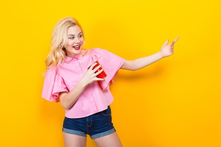 Portrait of attractive laughing blonde woman with red lips in pink shirt and jeans shorts with red plastic cup pose on orange background with copyspace call someone to come. Stock Photo