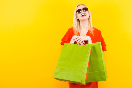 Portrait of attractive happy blonde woman in red dress and sunglasses isolated on yellow background holding colourful shopping paper bags.