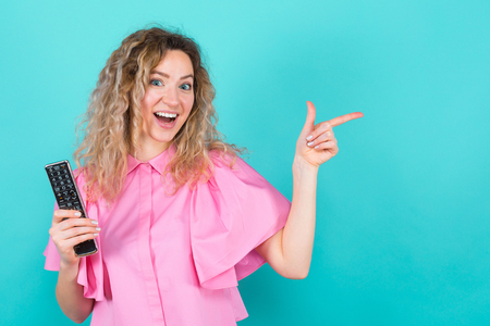 Portrait of attractive curly-haired woman in pink blouse isolated on blue backgroung holding remote control and showing with her finger to left turning TV over concept.