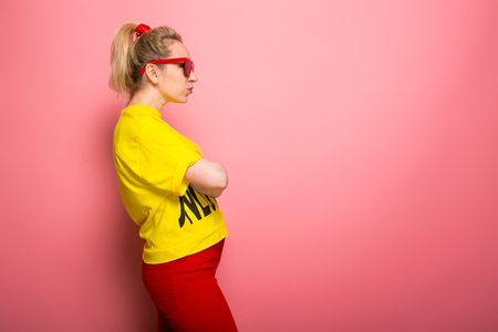 Attractive woman in yellow T-shirt, red jeans and sunglasses standing sideways with arms crossed isolated on pink background with copyspace.