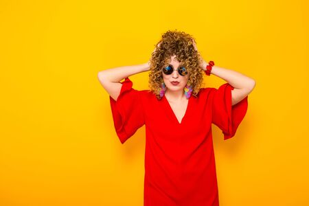 Portrait of a white woman with afrro curly hairstyle in red dress and sunglasses touching her head isolated on orange background with copyspace beauty salon advertisement concept. Stock Photo