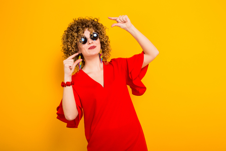 Portrait of a white woman with afrro curly hairstyle in red dress and sunglasses showing a little bit sign isolated on orange background with copyspace.