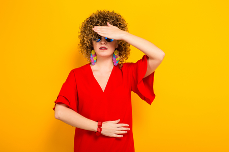 Portrait of a white woman with afrro curly hairstyle in red dress and sunglasses hiding behind her palm isolated on orange background with copyspace.
