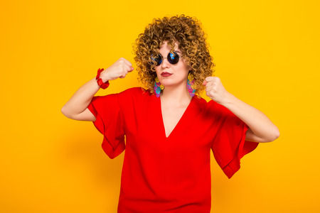 Portrait of a white woman with afrro curly hairstyle in red dress and sunglasses showing her muscles ready to fight isolated on orange background with copyspace. Stock Photo
