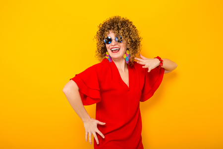 Portrait of a white woman with afrro curly hairstyle in red dress and sunglasses dancing isolated on orange background with copyspace beauty salon advertisement concept. Stock Photo