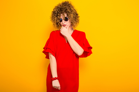Portrait of a white woman with afrro curly hairstyle in red dress and sunglasses propping up her chin isolated on orange background with copyspace beauty salon advertisement concept.