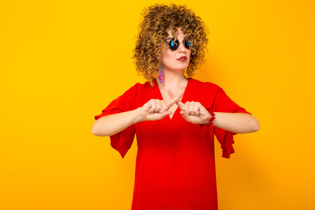 Portrait of a white woman with afrro curly hairstyle in red dress and sunglasses with fingers crossed isolated on orange background with copyspace beauty salon advertisement concept.