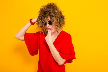 Portrait of a white woman with afrro curly hairstyle in red dress and sunglasses holding two fingers in mouth to vomit isolated on orange background with copyspace feeling sick concept.