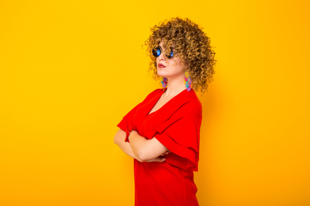 Portrait of a white woman with Afro curly hairstyle in red dress and sunglasses standing sideways with arms crossed isolated on orange background