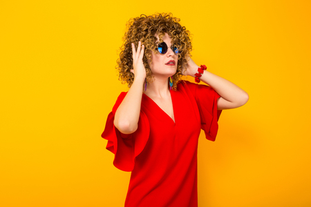 Portrait of a white woman with Afro curly hairstyle in red dress and sunglasses touching her hair isolated on orange background