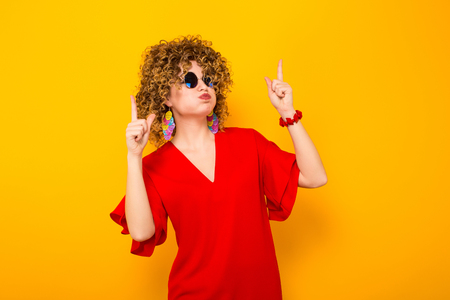Portrait of a white woman with Afro curly hairstyle in red dress and sunglasses pointing with fingers upwards isolated on orange background