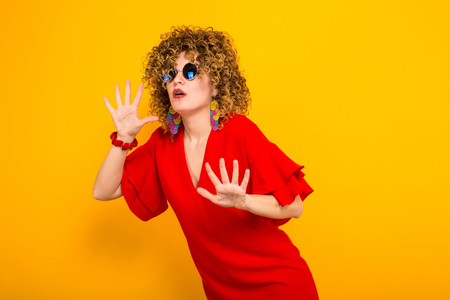 Portrait of a white scared woman with Afro curly hairstyle in red dress and sunglasses holds palms in front of her isolated on orange background Stock Photo