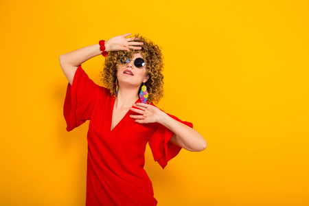 Portrait of a white woman with Afro curly hairstyle in red dress and sunglasses holds palm near forehead in shock isolated on orange background Stock Photo