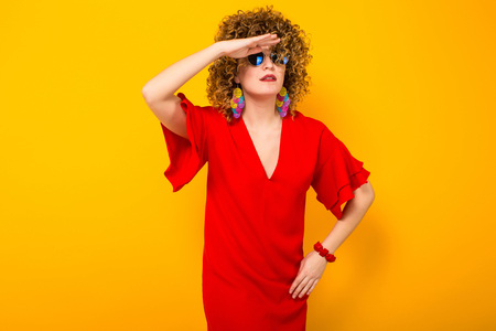 Portrait of a white woman with Afro curly hairstyle in red dress and sunglasses looking somewhere with palm above eyes isolated on orange background Stock Photo