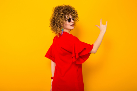 Portrait of a white woman with Afro curly hairstyle in red dress and sunglasses showing rock sign gesture isolated on orange background
