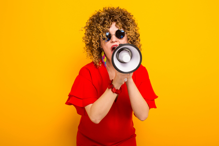 Portrait of a white woman with Afro curly hairstyle in red dress and sunglasses speaking into megaphone isolated on orange background