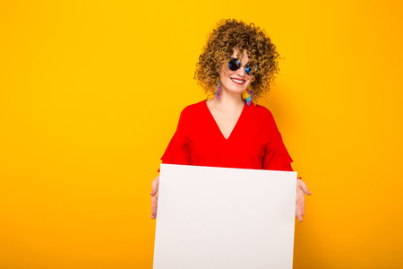 Portrait of a white woman with Afro curly hairstyle in red dress and sunglasses holding white blank board isolated on orange background