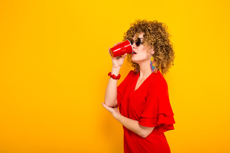 Portrait of a white woman with Afro curly hairstyle in red dress and sunglasses drinking from red plastic cup with drink isolated on orange background Stock Photo