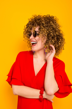 Close up portrait of a white woman with Afro curly hairstyle in red dress and sunglasses touching her hair isolated on orange background