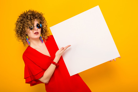 Portrait of a white woman with Afro curly hairstyle in red dress and sunglasses pointing at white blank board isolated on orange background