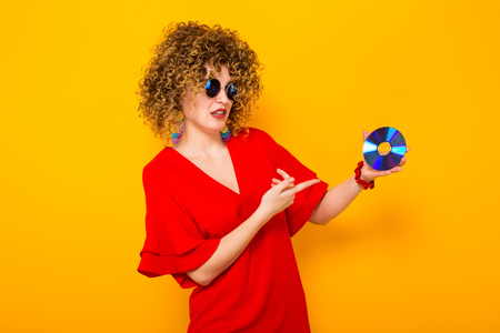 Portrait of a white woman with Afro curly hairstyle in red dress and sunglasses pointing at CD disc doesnt know what to do with it isolated on orange background