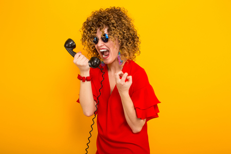 Portrait of a white angry woman with Afro curly hairstyle in red dress and sunglasses shouting at vintage phone isolated on orange background