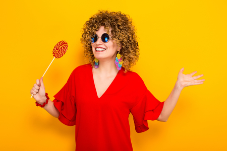 Portrait of a white woman with Afro curly hairstyle in red dress and sunglasses holding colorful lollipop isolated on orange background