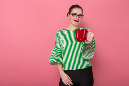 Portrait of attractive businesswoman with hair bun in striped blouse and eyeglasses offering red mug with beverage isolated on pink background with copyspace.