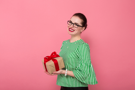 Portrait of attractive pleased businesswoman with hair bun in striped blouse and eyeglasses giving or taking gift box isolated on pink background with copyspace celebration womens day concept.