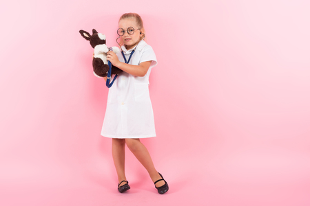 Portrait of little girl dressed like doctor in white coat and eyeglasses listening stethoscope to a plush rabbit isolated on pink background Stock Photo