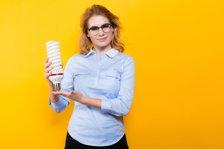 Portrait of attractive blonde woman in blue shirt and eyeglasses holding spiral light bulb isolated on yellow background Stockfoto