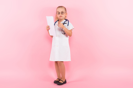Little girl dressed like doctor in white coat and glasses wear stethoscope and hold blank sheets and pen isolated on pink background Stock Photo