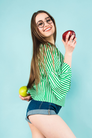 Portrait of attractive young long-haired girl in striped shirt, glasses and jeans shorts holding red and green apples isolated on blue background