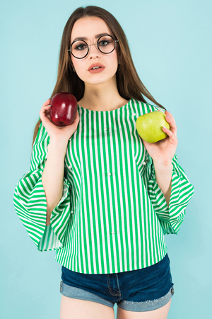 Close up portrait of attractive young long-haired girl in striped shirt, glasses and jeans shorts holding red and green apples isolated on blue background