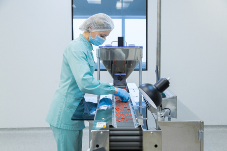 Pharmaceutical technician in sterile environment working on production of pills at pharmacy factory Stockfoto