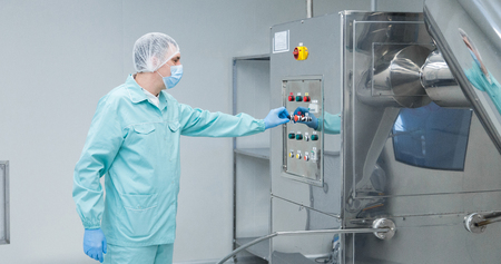 Pharmaceutical technician in sterile environment at pharmacy industry Foto de archivo