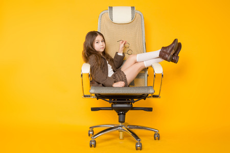 Portrait of long-haired little girl in eyeglasses sits in armchair wearing brown jacket, shorts and white knee-socks isolated on orange background with copyspace kids fashion concept.