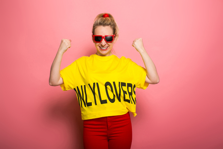 Woman in yellow T-shirt, red jeans and sunglasses holding fists up in excitment isolated on pink background with copyspace advertising winning concept.