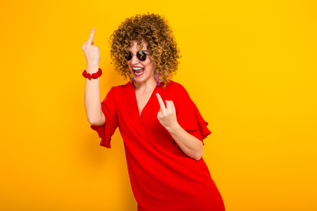 Portrait of a white woman with afrro curly hairstyle in red dress and sunglasses laughing and showing fuck sign isolated on orange background with copyspace beauty salon advertisement concept. 写真素材