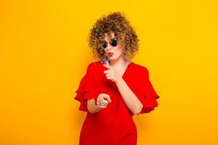Portrait of a white woman with afrro curly hairstyle in red dress and sunglasses pointing at camera isolated on orange background with copyspace beauty salon advertisement concept.
