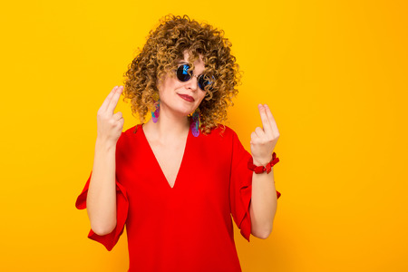 Portrait of a white woman with afrro curly hairstyle in red dress and sunglasses showing two fingers on both hands isolated on orange background with copyspace advertising concept. Stock Photo